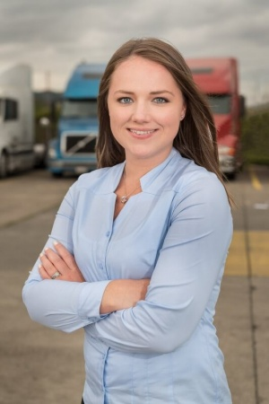 Professional headshot of corporate woman in parking lot pictured with company trucks and blue dress shirt.