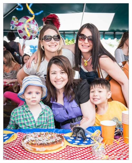 Friends and family of a four year old boy fighting cancer at his birthday party.