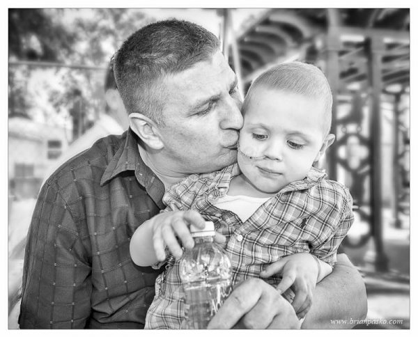 Father kissing his four year old son who is fighting cancer.