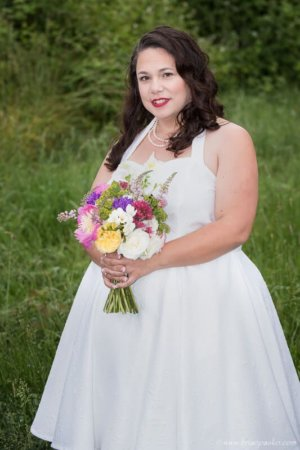 Portrait of a bride in a field of grass after a McMinnville, Oregon wedding .
