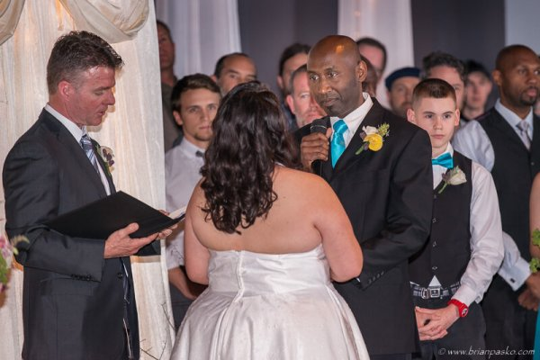 Groom saying vows to bride while flanked by groomsmen during a wedding in McMinville, Oregon.