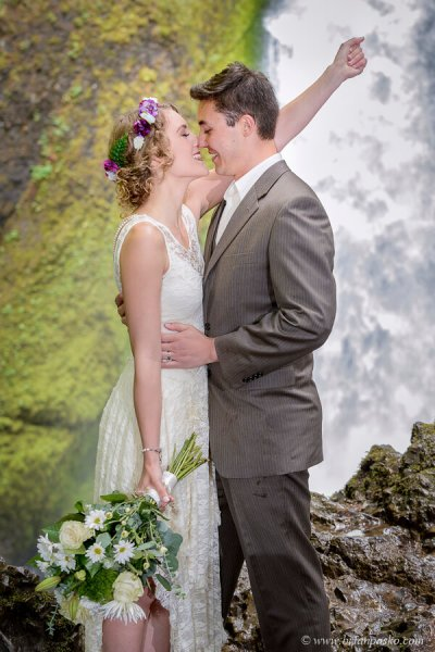 Bride celebrates first kiss with groom at Wahclella waterfall wedding in the Columbia Gorge.