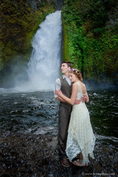 Groom holding bride while looking at Columbia Gorge after wedding at Wahlclella Waterfall.