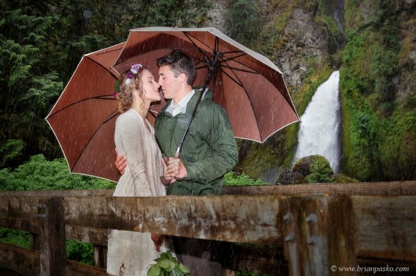 Bride and Groom kissing in rain after Columbia Gorge wedding at Wahlclella Waterfall.
