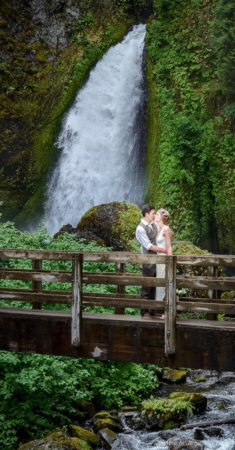 Bride and Groom kissing on bridge at Columbia Gorge wedding at Wahlclella Waterfall.