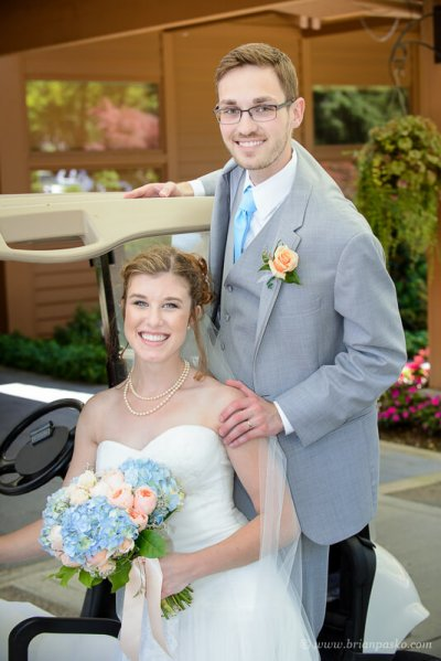 Portrait of a beautiful bride and groom sitting on golf cart after their summer wedding ceremony on Persimmon Golf Course in Oregon.