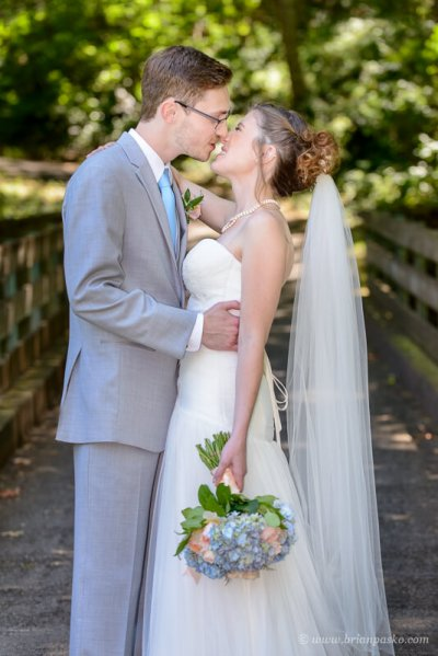 Portrait of a bride and groom kissing on a bridge at summer wedding ceremony on Persimmon Golf Course in Oregon.