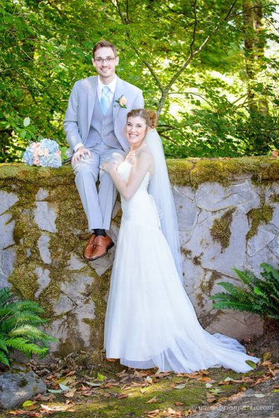 Portrait of a groom sitting on a rock wall with his bride at summer wedding ceremony on Persimmon Golf Course in Oregon.