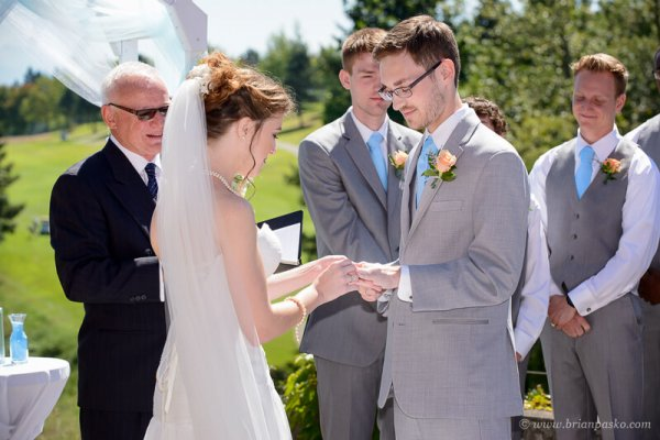 Portrait of a beautiful bride giving ring to her groom at summer wedding on Persimmon Golf Course in Oregon.