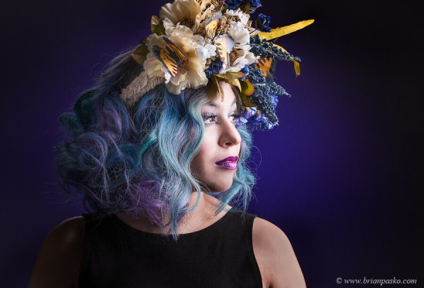 Low key fashion Portrait of beautiful model wearing butterfly hair piece and high fashion makeup.