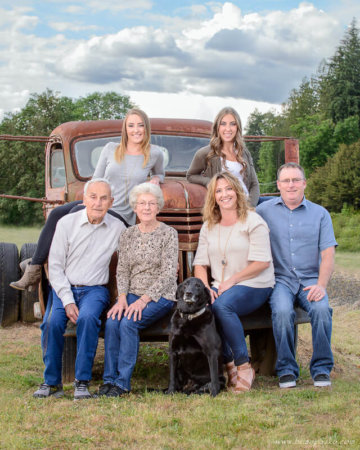 Family portrait of three generations with grandparents, parents, and adult daughters with labrador retriever dog on farm with old farm truck.