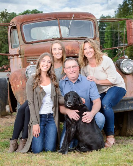 Family portrait of mom, dad, and two daughters on old farm truck with their labrador retriever dog.