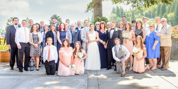 Portrait of a beautiful bride and groom with their family and wedding party at summer wedding on Persimmon Golf Course in Oregon.
