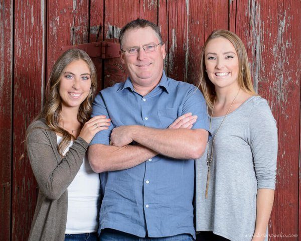 Portrait of a father and his two daughters on the family farm near a weathered red barn.