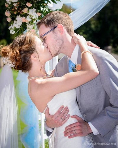 Portrait of a bride and groom during their first kiss at summer wedding on Persimmon Gold Course in Oregon.