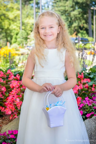 Portrait of a beautiful flower girl at summer wedding on Persimmon Golf Course in Oregon.