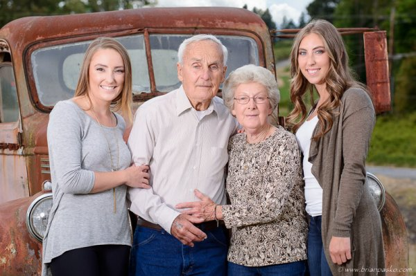 Grandparents and Granddaughters with family portrait on old farm truck.