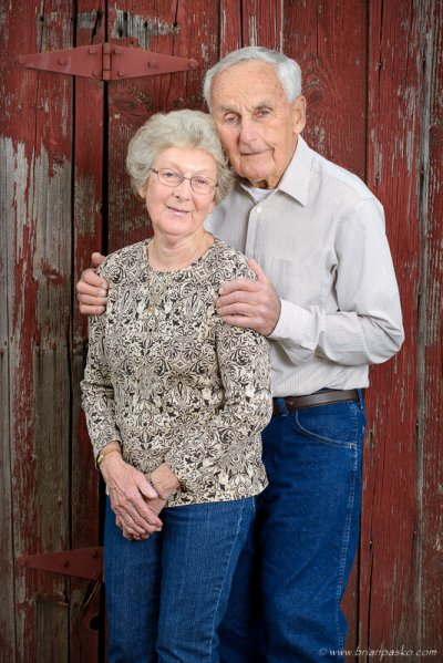 Portrait of aging grandparents on the family farm against a weather red barn.