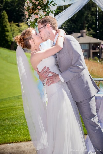 Portrait of a groom dipping his bride during first kiss at summer wedding on Persimmon Gold Course in Oregon.