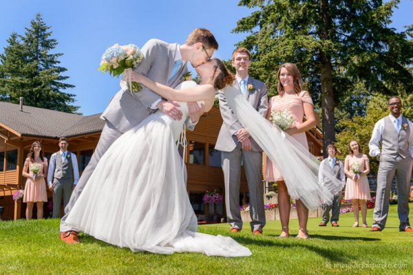 Portrait of a groom dipping his bride for a kiss at their summer wedding ceremony on Persimmon Golf Course in Oregon.