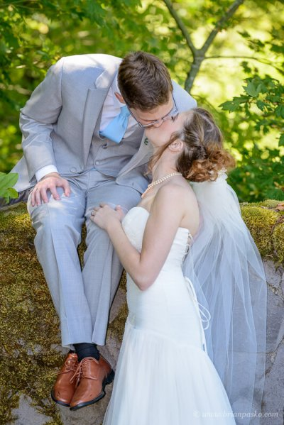Portrait of a groom kissing with his bride on rock wall at summer wedding ceremony on Persimmon Golf Course in Oregon.