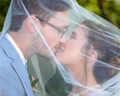 Portrait of a bride and groom kissing under her veil at summer wedding ceremony on Persimmon Golf Course in Oregon.