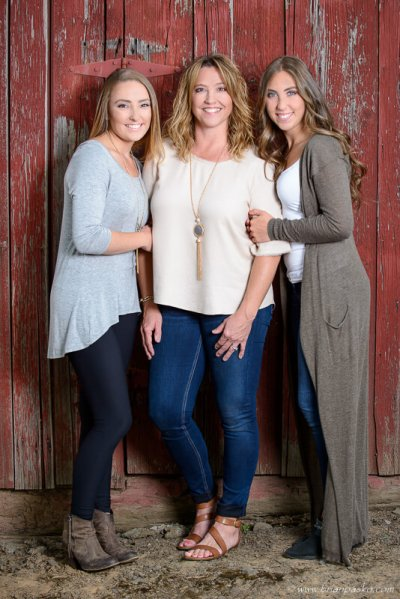 Portrait of a mother and her two daughters on the family farm near a weathered red barn.