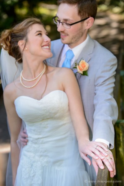 Portrait of a bride and groom with focus on hands and wedding rings at summer wedding ceremony on Persimmon Golf Course in Oregon.