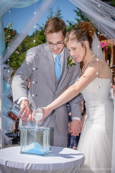 Portrait of a bride and groom pouring sand during their summer wedding ceremony on Persimmon Golf Course in Oregon.