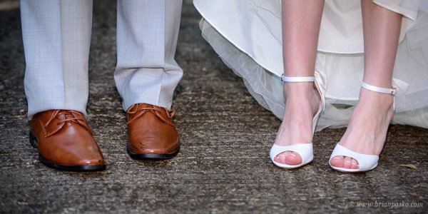 Portrait of a the feet and shoes of a bride and groom during their summer wedding ceremony on Persimmon Golf Course in Oregon.