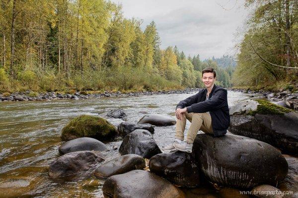 Environmental portrait of a Sandy High School Senior boy sitting on rocks along Sandy River, Oregon.
