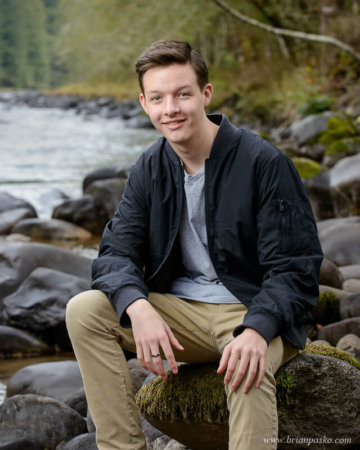 Sandy High School Senior boy sitting on rocks along Sandy River, Oregon.