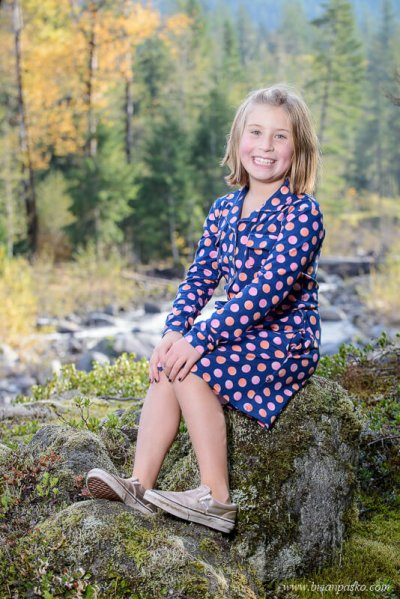 Family portrait of a girl wearing a blue and pink polka dot dress near the Sandy River in fall.