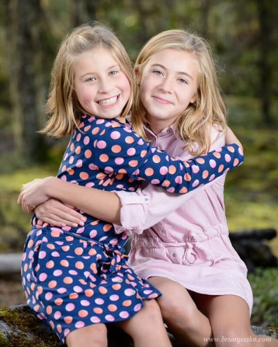 Family portrait of two sisters with girls hugging in the forest near the Sandy River wearing dressing in fall.