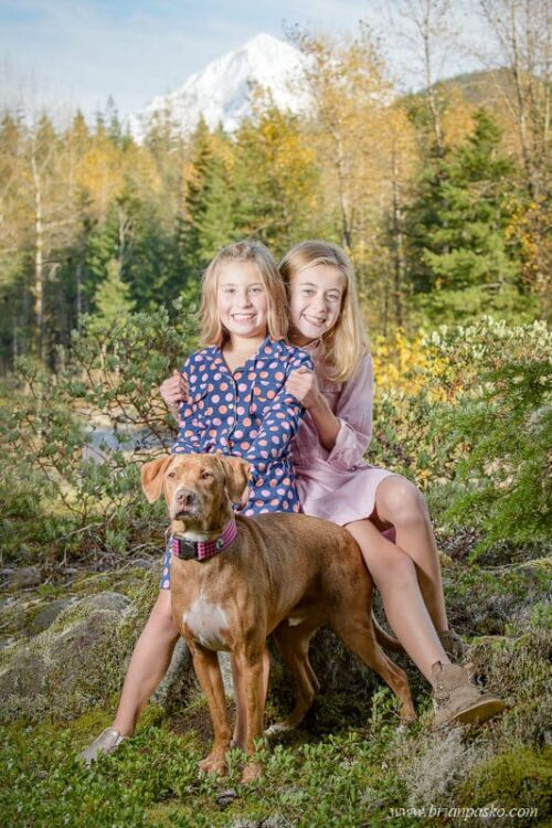 Family portrait of two sisters and their dog with girls wearing dresses near the Sandy River with Mount Hood in fall.