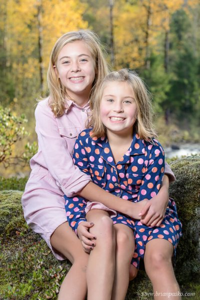 Family portrait of two sisters wearing pink and blue dresses near the Sandy River in fall.