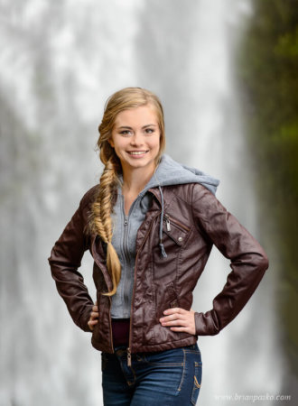 Stunning waterfall background for portrait of a Sunset High School senior girl with picture at Horsetail falls in the Columbia Gorge.