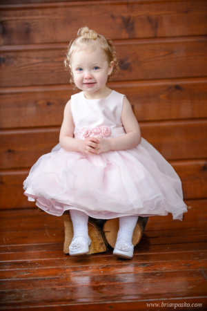 Portrait of a two year old girl in a pink dress sitting on a wooden porch.