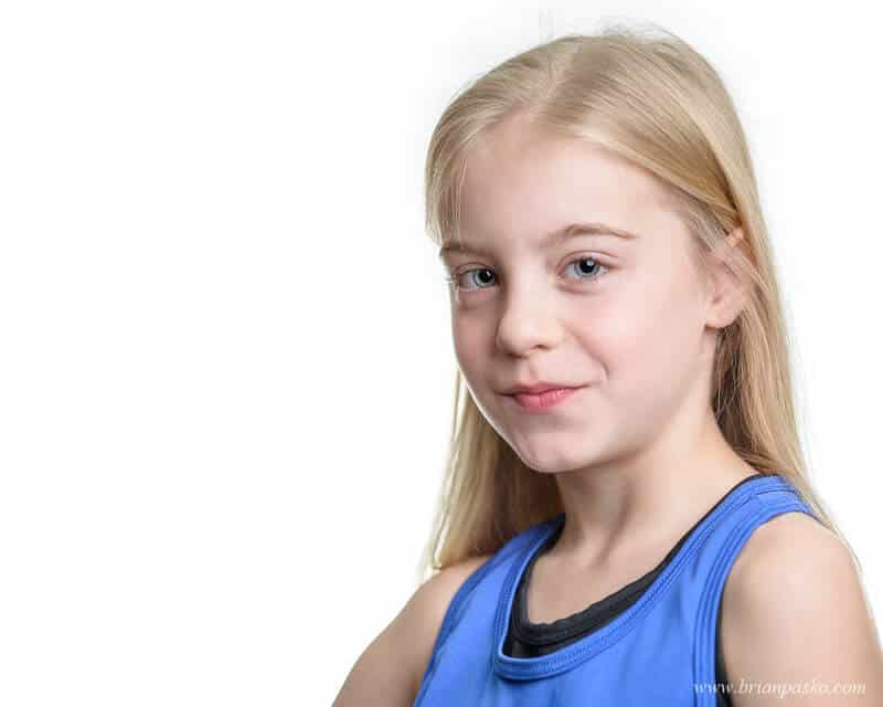 Headshot portrait of an eight year old competitive dancer girl wearing blue on white background.