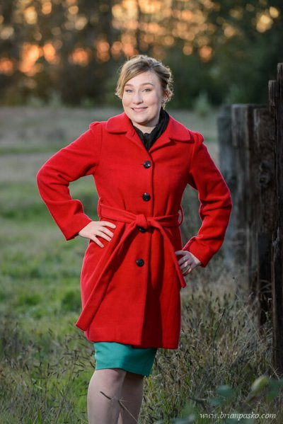 Portrait of a Glencoe High School senior girl in a field at sunset wearing a red coat.