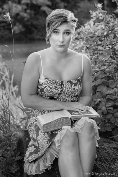 Portrait of a Glencoe High School senior girl reading a vintage book near a lake in black and white picture.