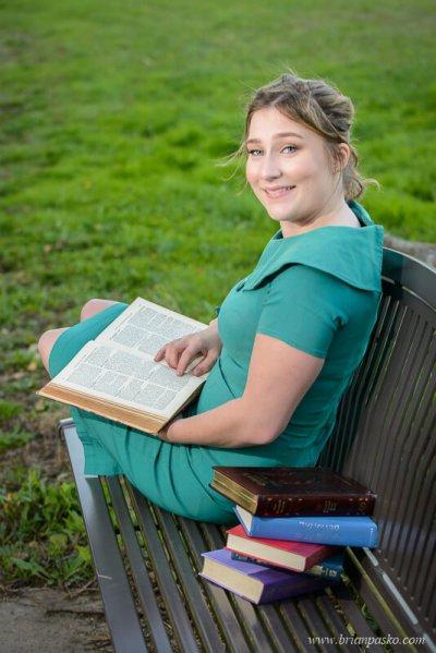 Senior Portrait of a Glencoe High School girl reading vintage books on a park bench.