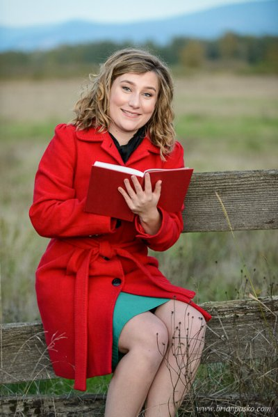 Picture of Glencoe High School senior girl with senior portrait reading a vintage book in a field.