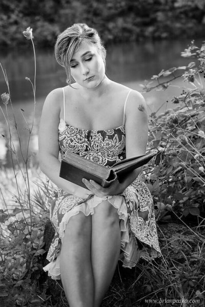Picture of Glencoe High School senior girl with black and white senior portrait reading a vintage book near a lake.