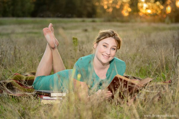 Portrait of a Glencoe High School senior girl with senior picture reading vintage books in a field at sunset.