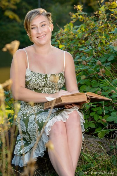 Picture of Glencoe High School senior girl with senior portrait reading a vintage book near a lake.