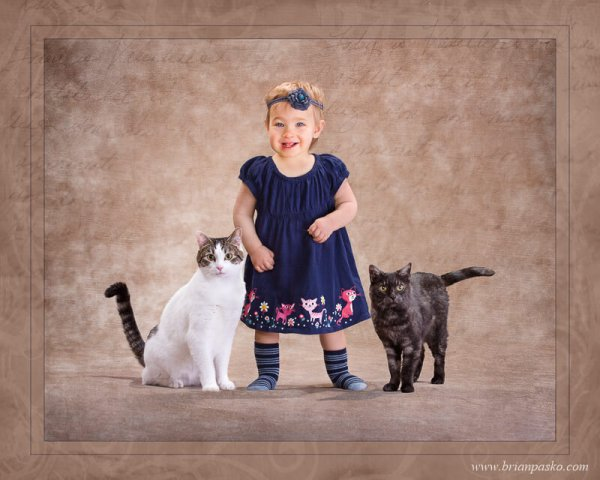 Portrait of one year old baby in a cat dress standing with her two pet cats.