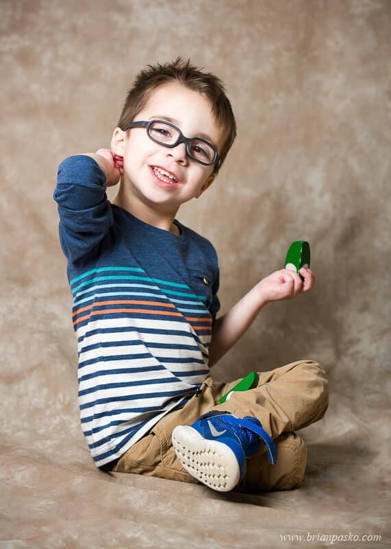 Portrait of a four year-old autistic boy on textured backdrop with toys.