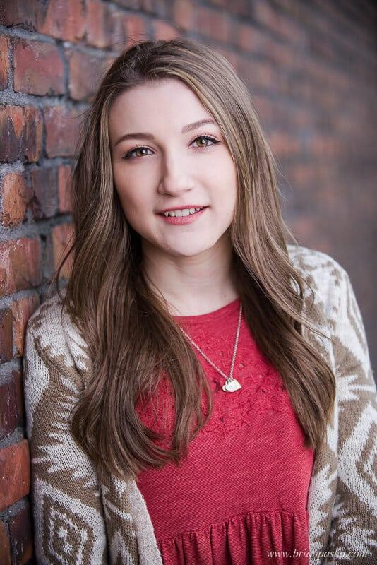 Hillsboro High School senior portrait of girl leaning against a red brick wall in Portland, Oregon.
