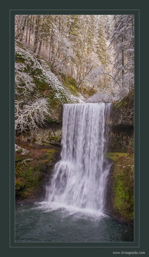 Lower South Falls in winter with dusting of snow and evening forest light at Silver Falls State Park near Silverton, Oregon.